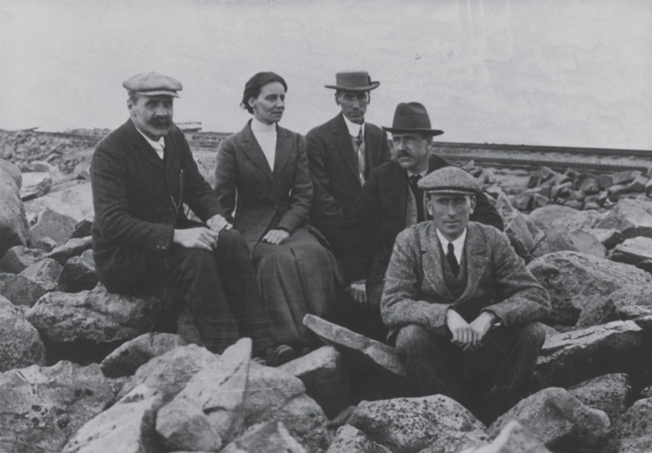Mabel sitting on rocks atop Pike's Peak with Haldane and C G Douglas and two other researchers