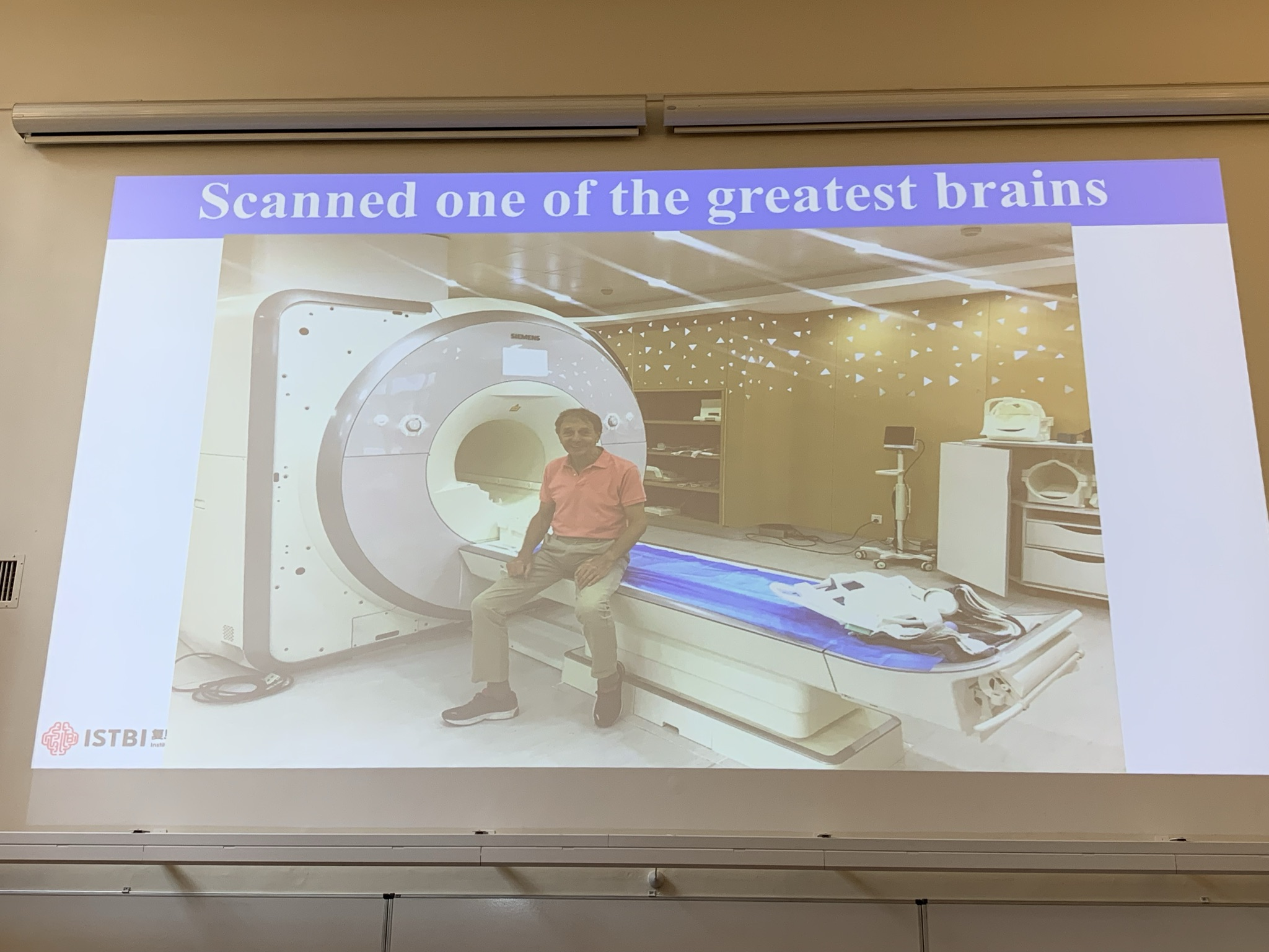 Colin Blakemore sitting on MRI machine following a scan.