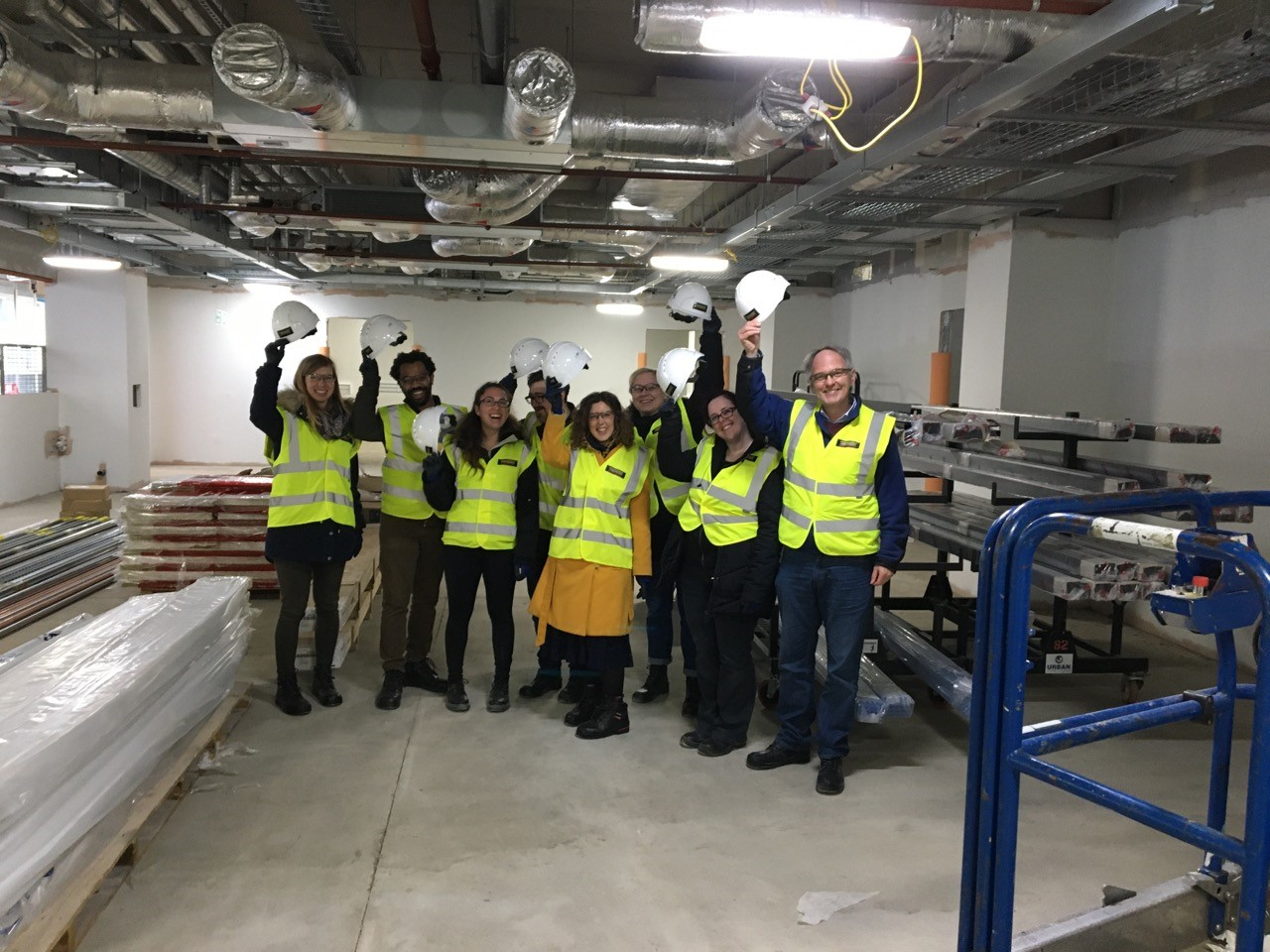 8 OPDC researchers including Director Richard Wade-Martins, Dayne Beccano-Kelly and Natalie Connor Robson hold hard hats