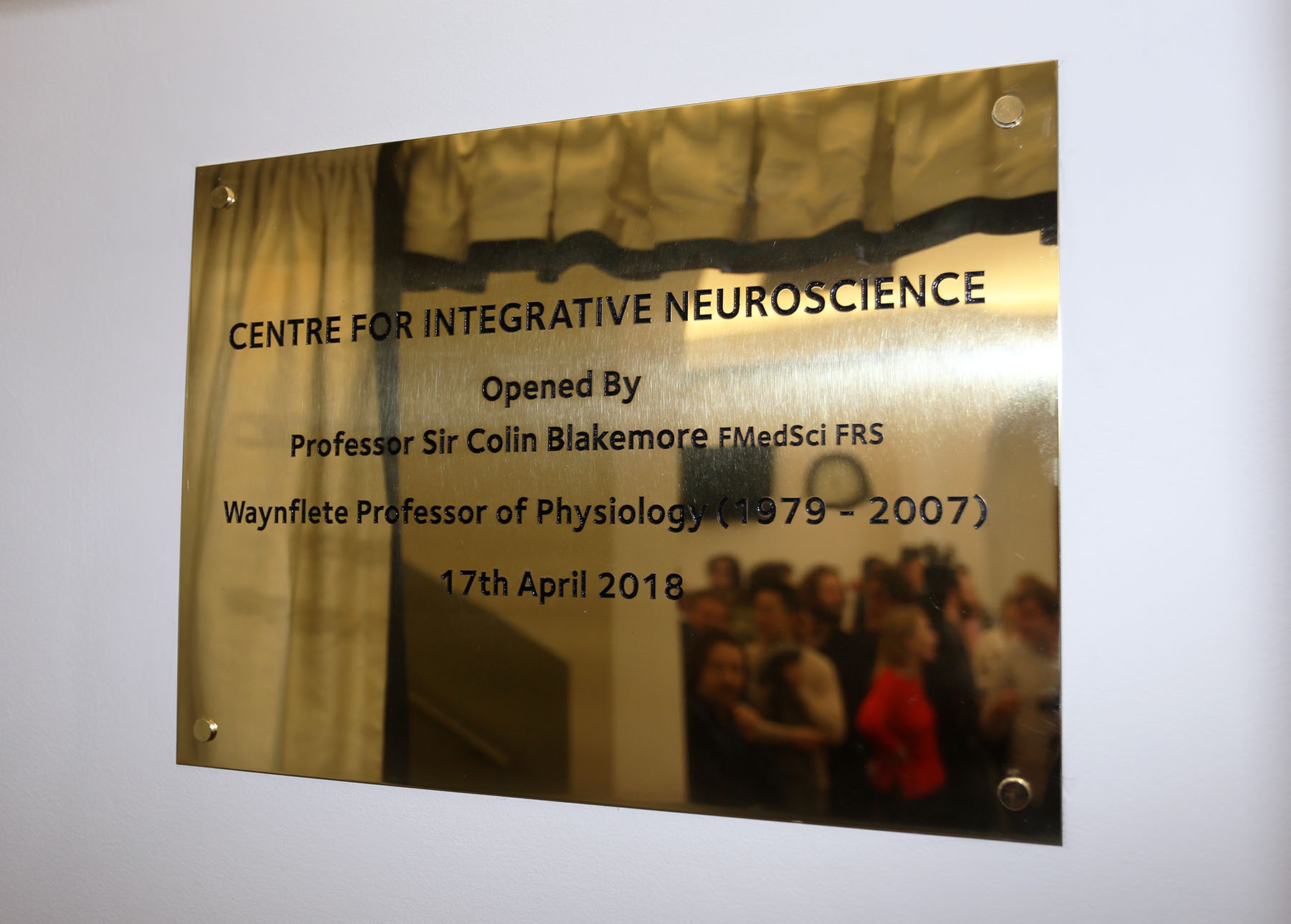Plaque with reflection of people in reception.jpg