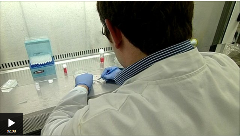 Screen shot of male scientist in white coat working on a petri dish in the lab