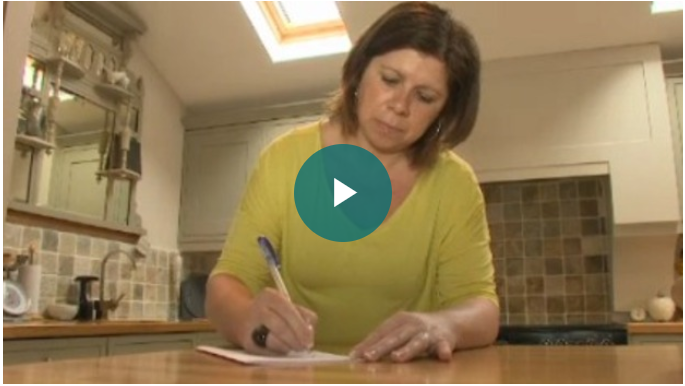 Video screenshot of woman in kitchen writing in a notepad